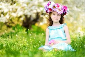 Adorable little girl in blooming cherry garden