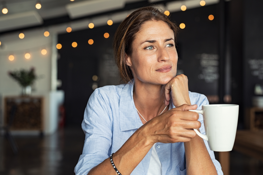 Thoughtful,Mature,Woman,Sitting,In,Cafeteria,Holding,Coffee,Mug,While