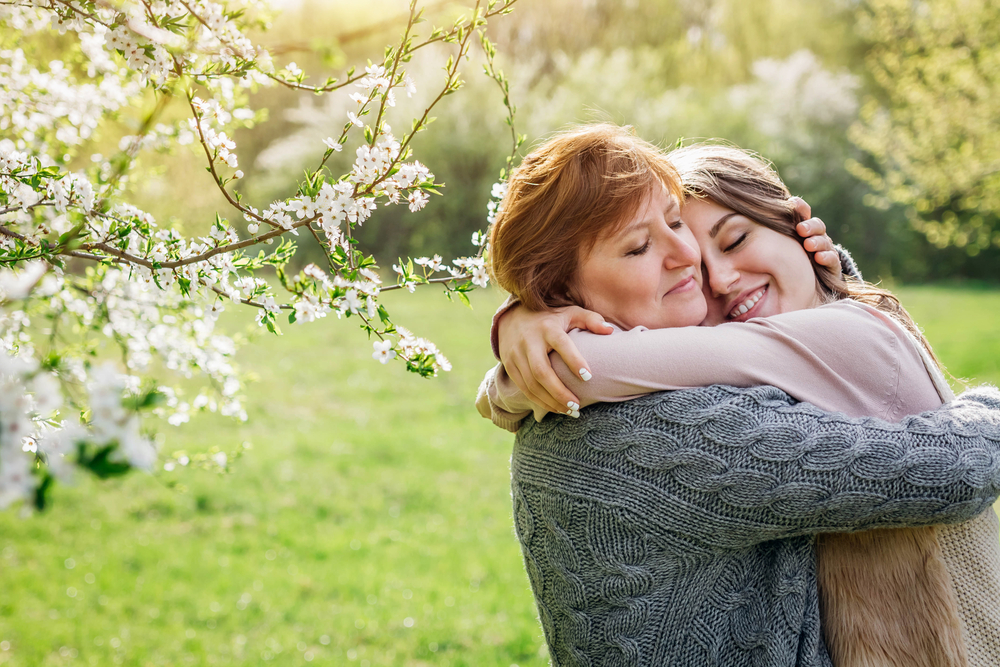 Middle-aged,Mother,And,Her,Daughter,Hugging,In,Blooming,Spring,Garden.