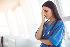 Beautiful,Doctor,In,Blue,Scrubs,Is,Covering,Her,Face,While