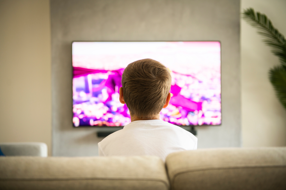 Back,View,Image,Of,Cute,Boy,Sitting,On,Sofa,And
