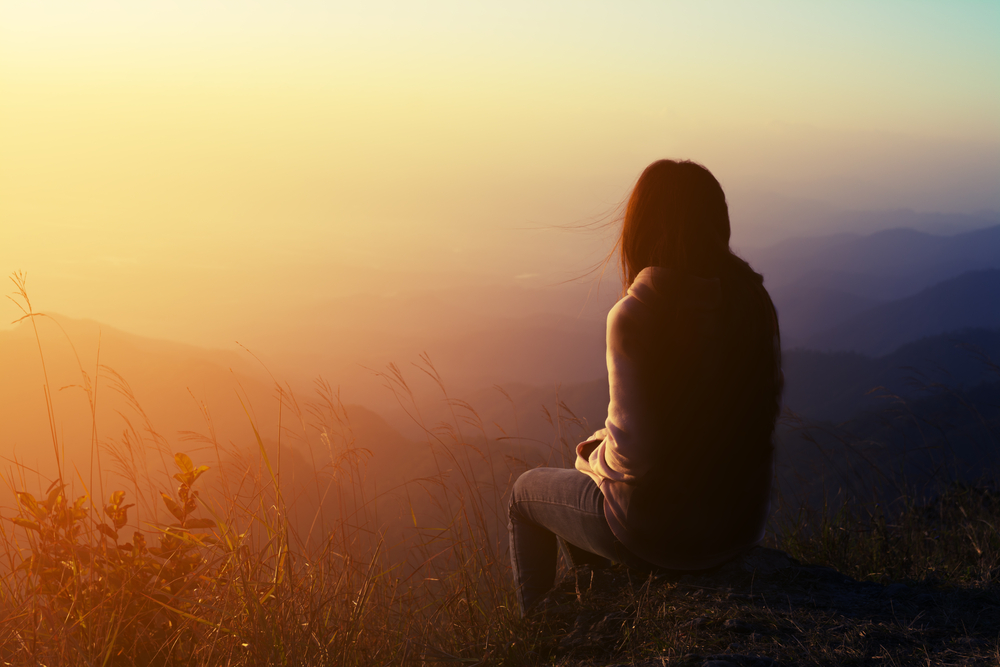 Silhouette,Woman,Sitting,On,Mountain,In,Morning,And,Vintage,Filter